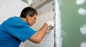 Man applying ceramic tile to a bathtub enclosure wall.
