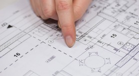 Finger from an unknown person is showing in the plan of the house.